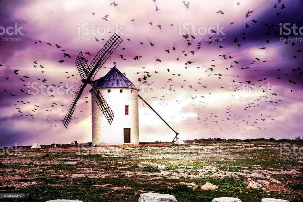 Flock of birds and windmill at dusk. stock photo