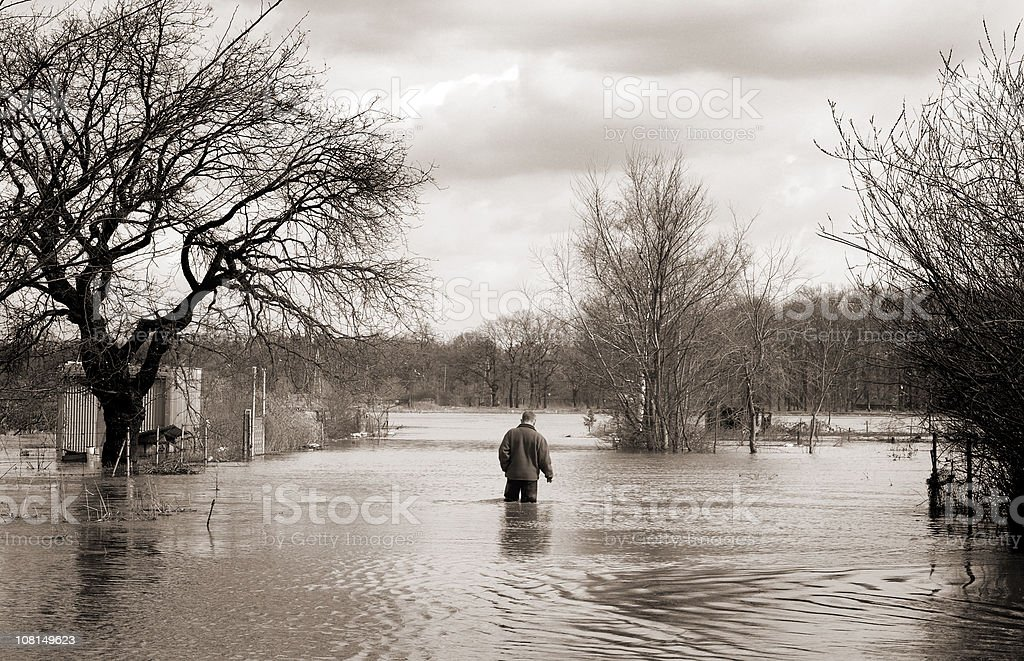 flood man walking alone through the high water royalty-free stock photo