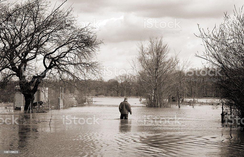 flood man walking alone through the high water stock photo