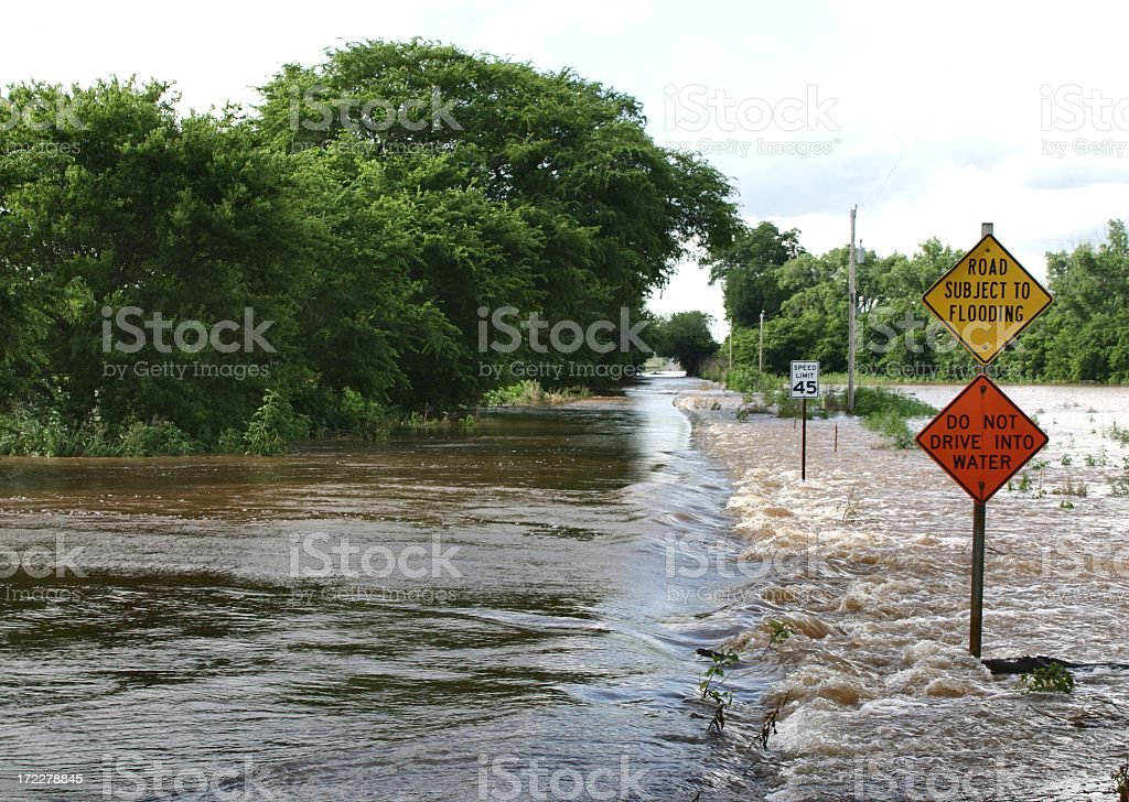 Flooded Road in country with trees and signs Horizontal royalty-free stock photo
