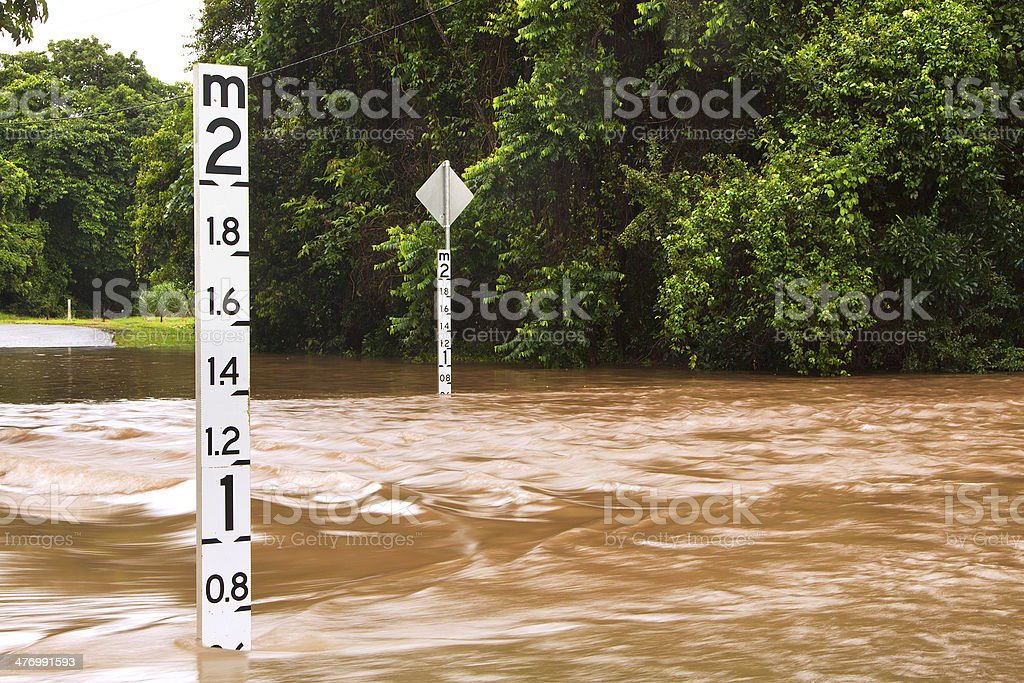 Flooded road with depth indicators in Queensland, Australia stock photo