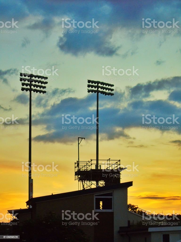 Floodlights silhouetted at sunset of sport ground stock photo