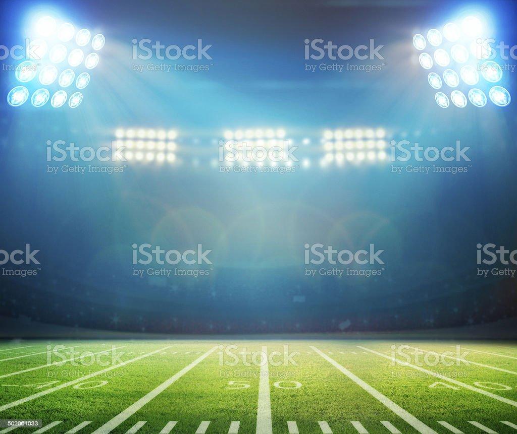 floodlit football stadium with closeup on field stock