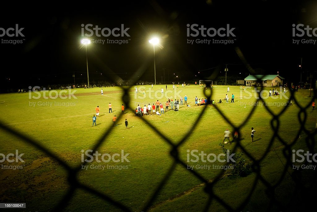 floodlit soccer field through chainlink fence royalty-free stock photo