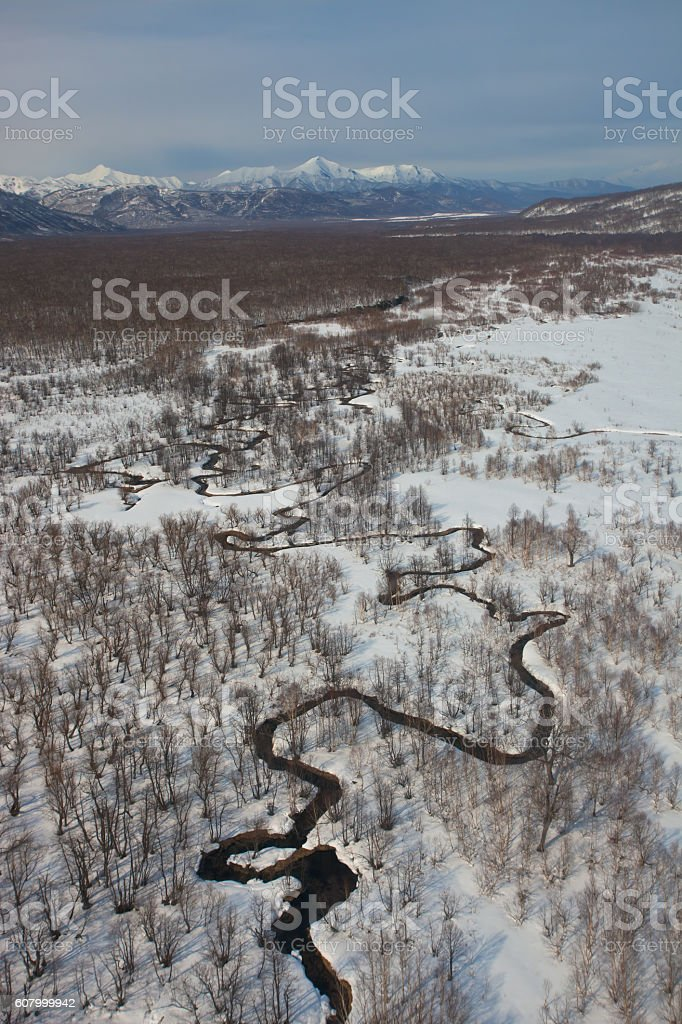 Floodplain of the river meanders in a mountain snowy tundra stock photo