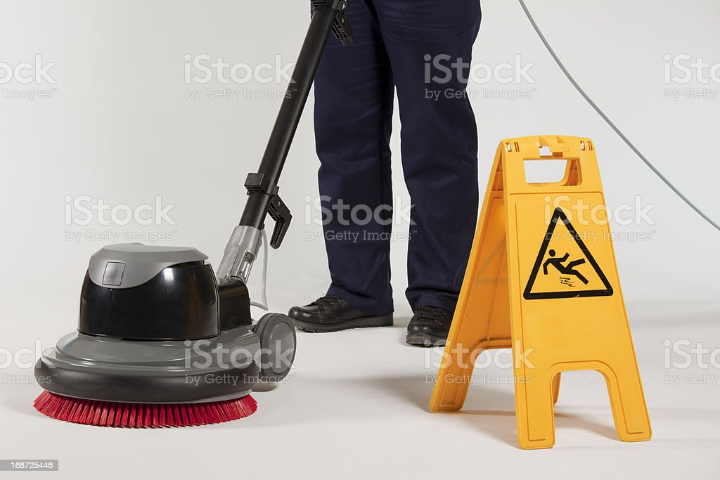 Floor cleaner near wet floor sign and worker's legs royalty-free stock photo