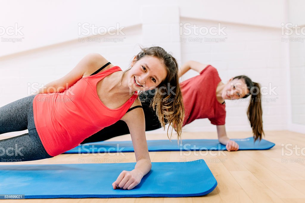 Two teenaged girls adopt the \'side plank\' position in an exercise...