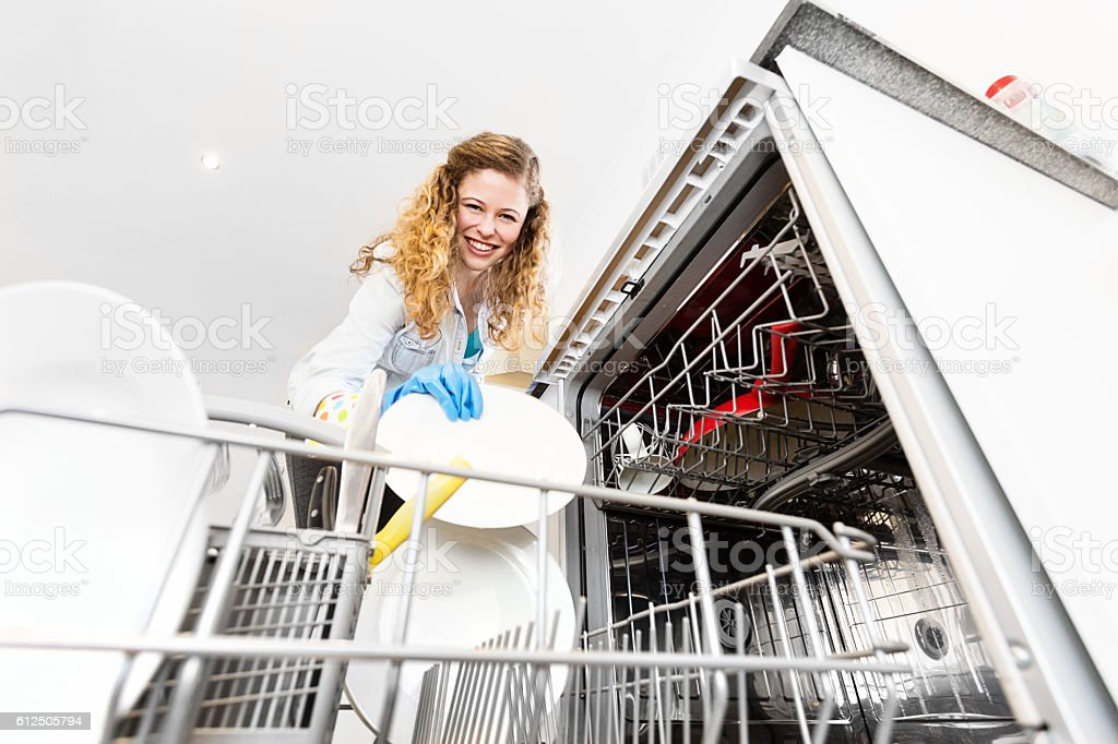 Floor level look up at pretty girl loading dishwasher stock photo