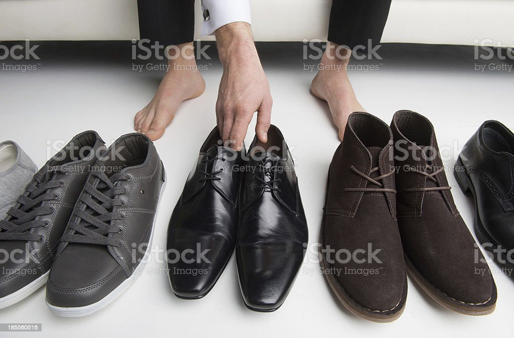 Floor view of a man's bare feet choosing from a row of shoes stock photo