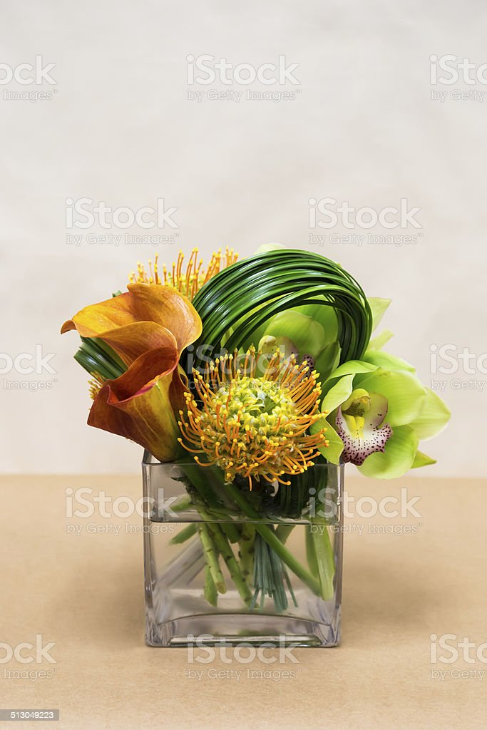 Floral arangement with Calla Lilies, cymbidium, protea and green stock photo