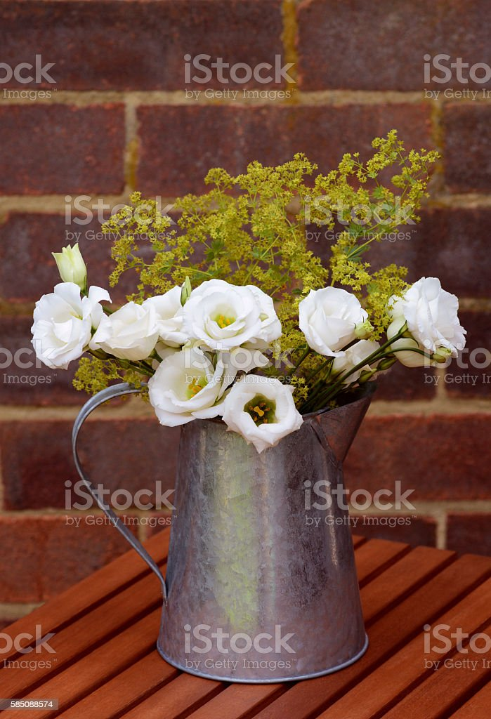 Floral arrangement of white prairie gentians in a vintage jug stock photo