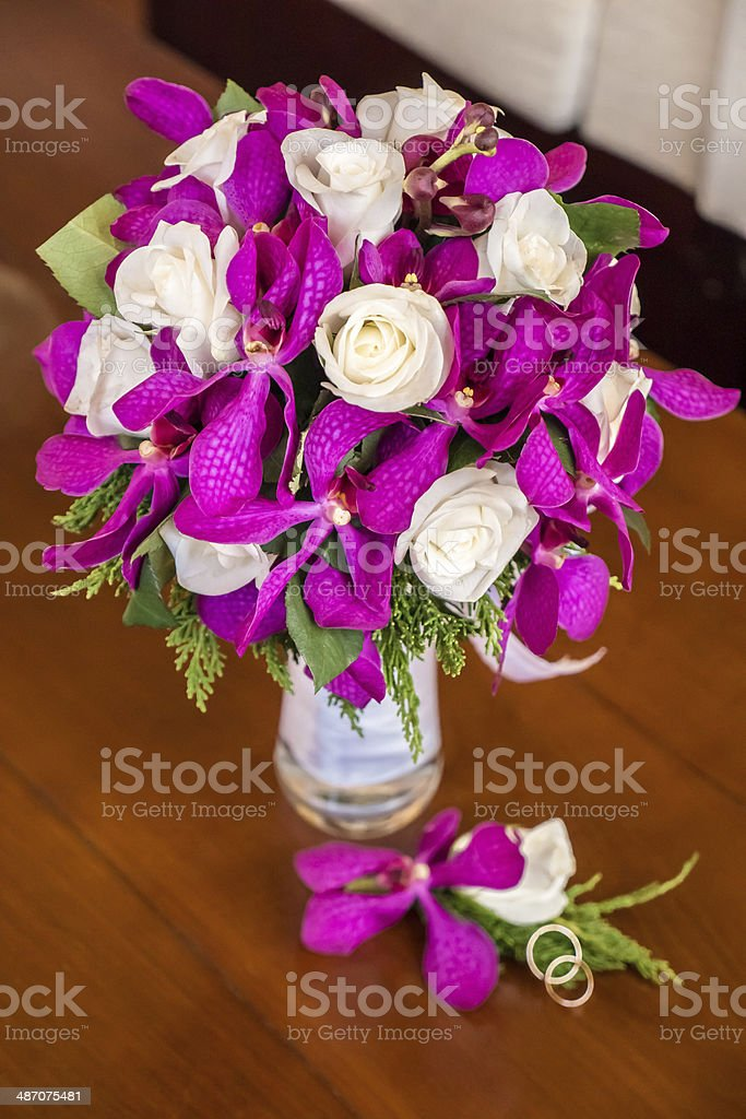 floral bouquet of roses and orchids with rings stock photo