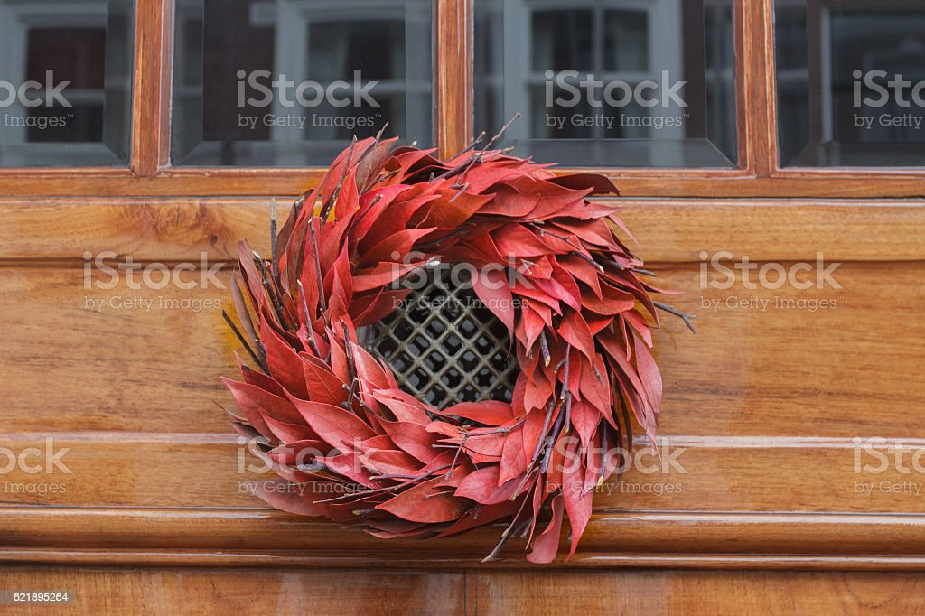 Floral red outdoor Christmas wreath hanging at entrance door stock photo