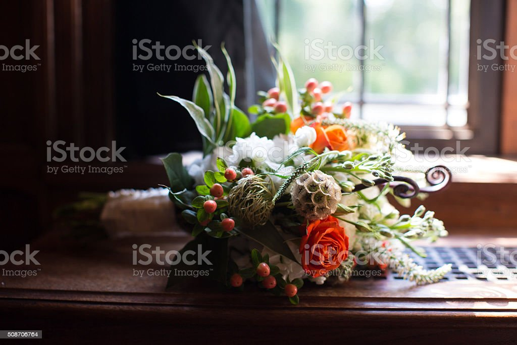 Floral wedding bouquet in window sill with sunshine pouring in stock photo