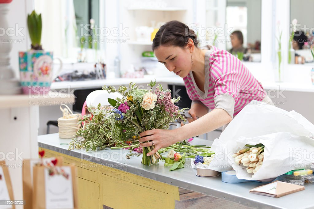 Florist at work assembling a beautiful flower bouquet stock photo