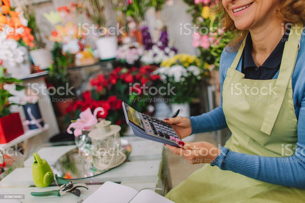 Photo of mid-adult florist woman, calculating expenses in her floral...