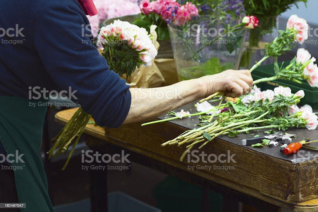 A florist creating a bouquet on a wooden table stock photo