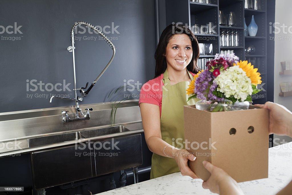 Florist Handing Merchandise to Customer in Flower Shop royalty-free stock photo