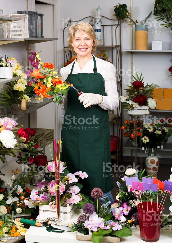 Florist in apron holding scissors and fixing flowers stock photo