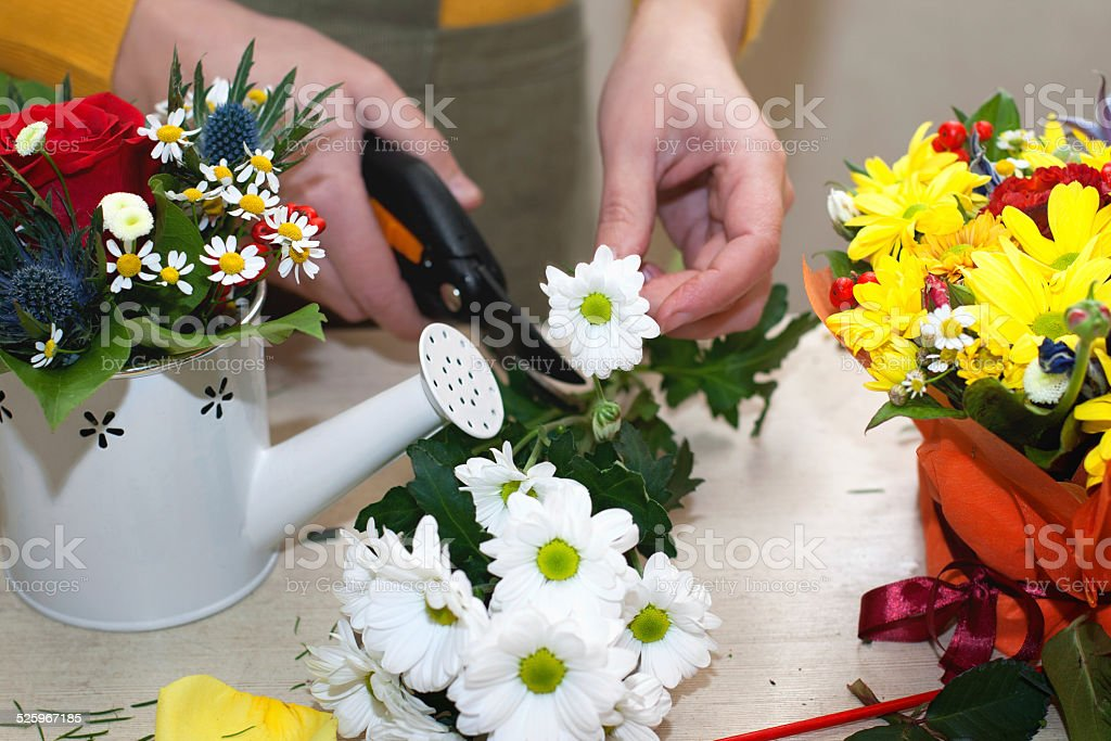 Florist making composition of different cut flowers stock photo