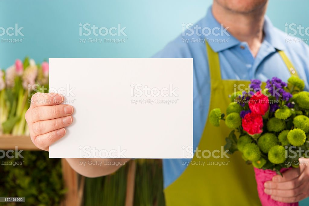 Florist showing a blank white sign royalty-free stock photo