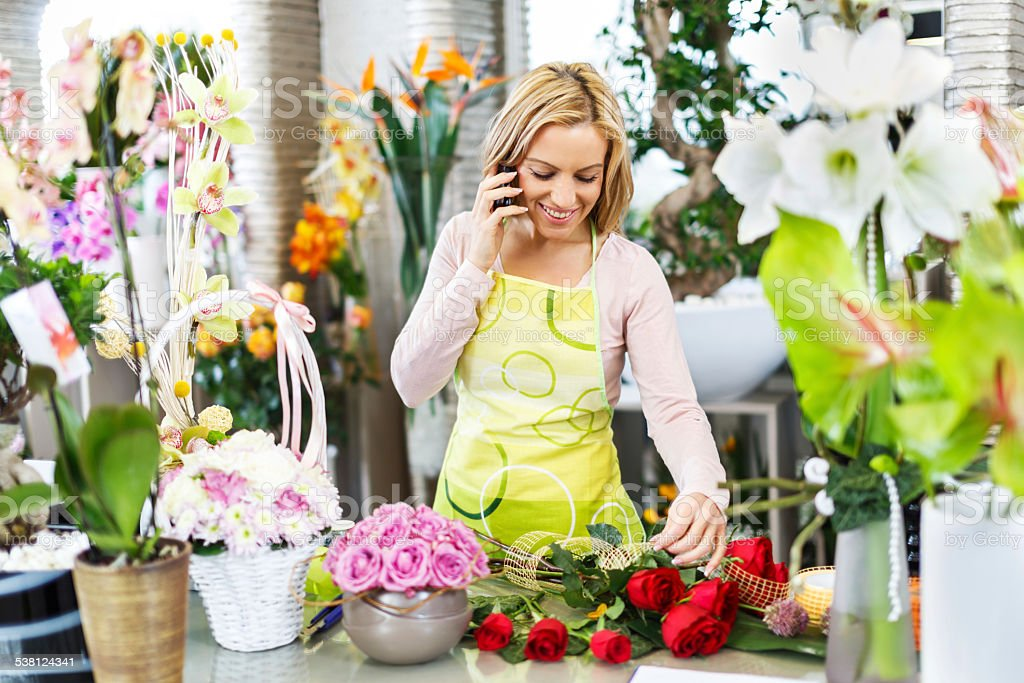 Florist using cell phone in a flower shop. stock photo