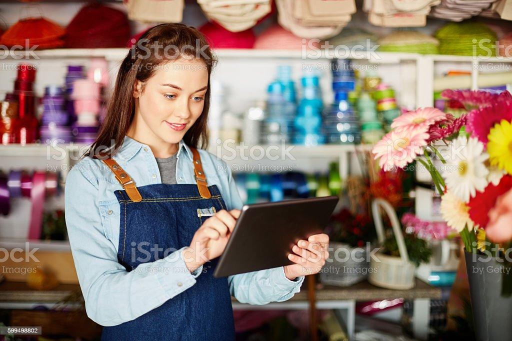 Florist using digital tablet in flower shop stock photo