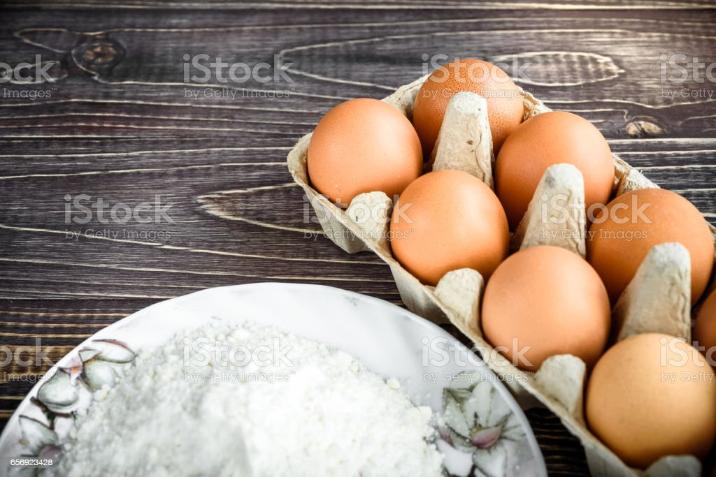 flour and eggs for pastries on a wooden background, retro style stock photo