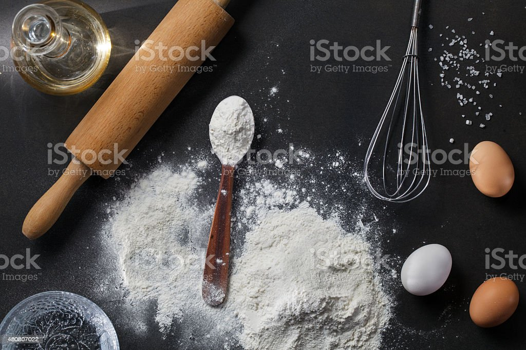 flour and ingredients on black table stock photo