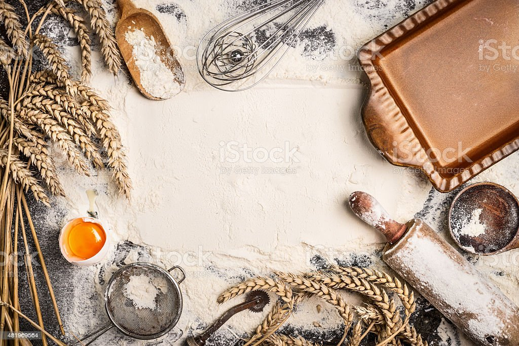 flour baking background with raw egg, rolling pin, wheat ear stock photo