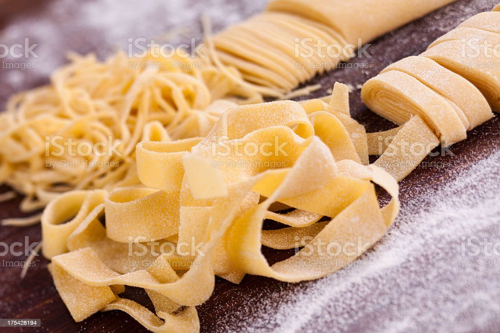 Flour blushed spaghetti and tagliatelli on brown table stock photo