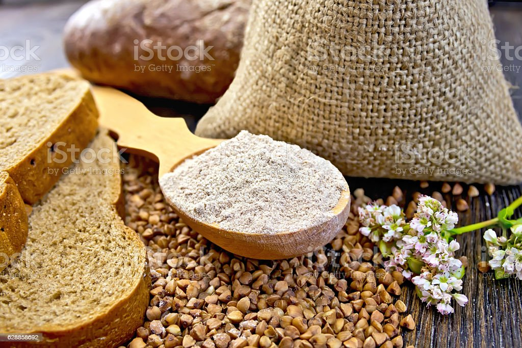 Flour buckwheat in spoon with cereals and bread on board stock photo