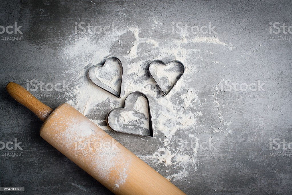Flour, cookie cutters and rolling pin on a stone table stock photo