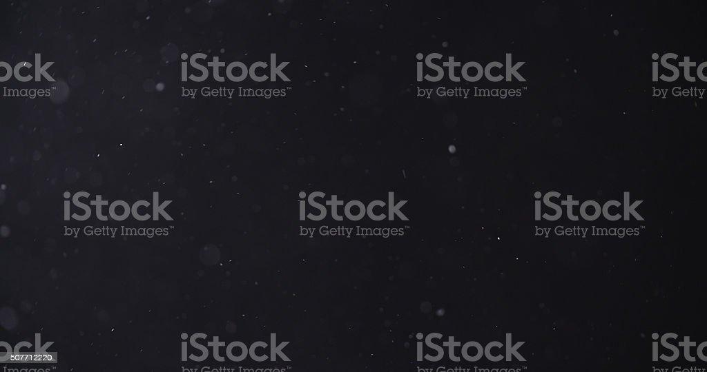 flour dust particles on black background stock photo