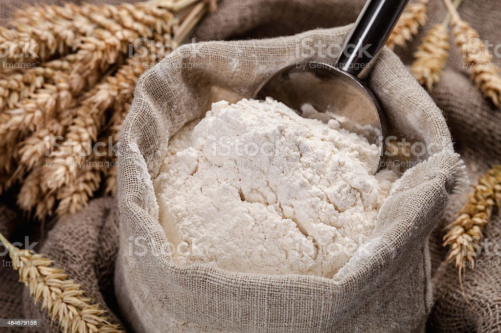 Flour in a bag on the table and spikelets stock photo