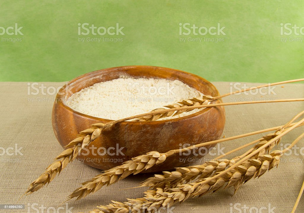 Flour in a wooden bowl with ears of wheat stock photo