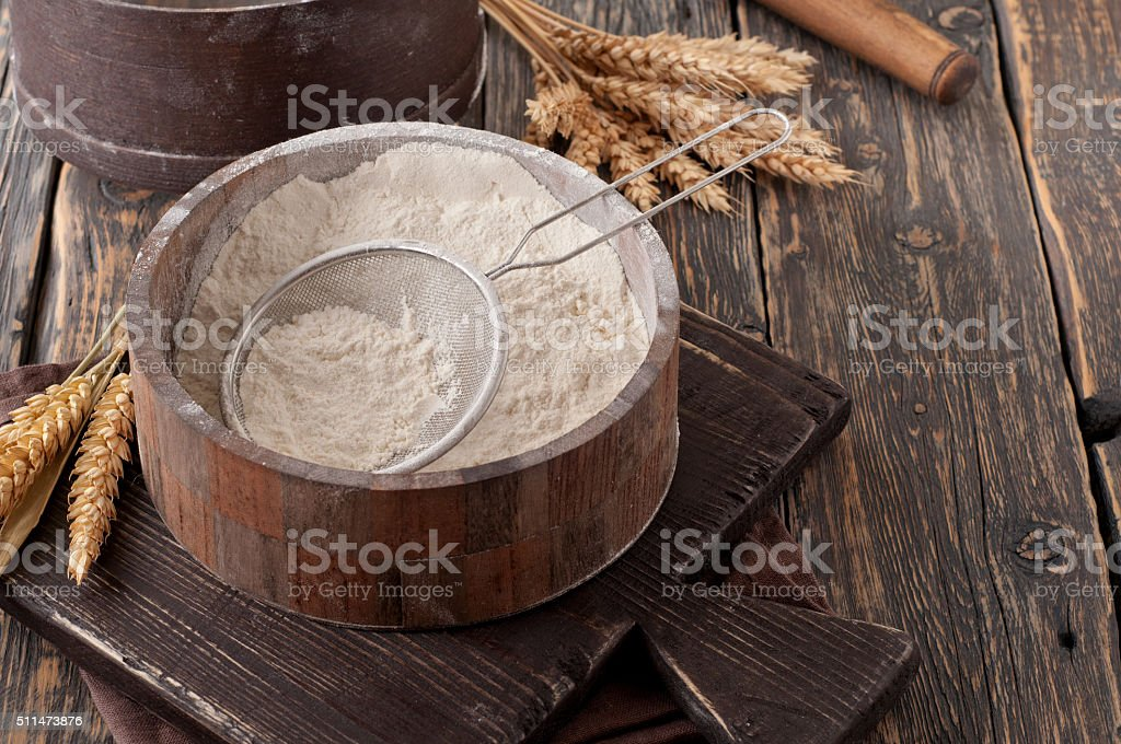 Flour in a wooden bowl with sieve on vintage board stock photo