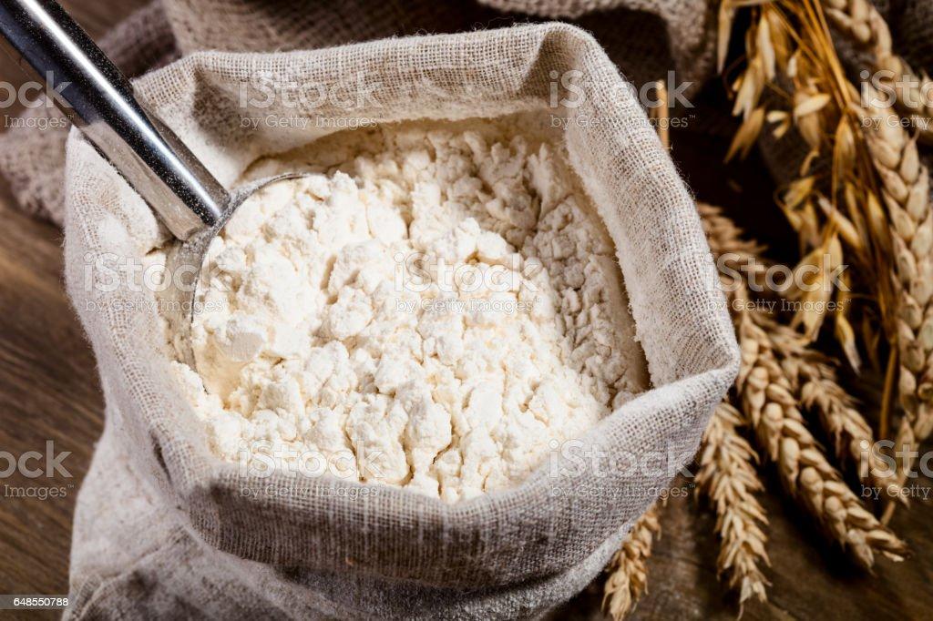Flour in burlap sack with scoop of metal stock photo