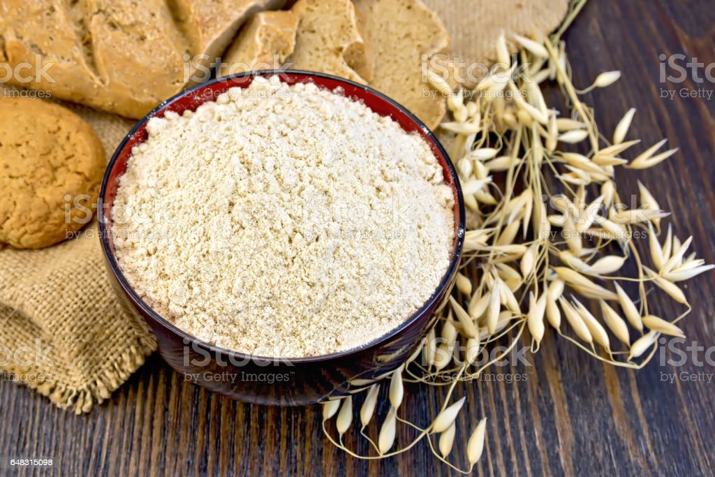 Flour oat in bowl with bread on sackcloth and board stock photo