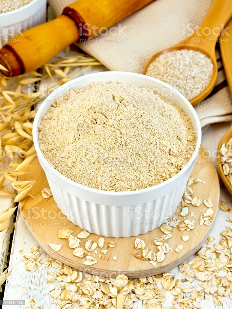 Flour oat in white bowl with bran and flakes stock photo