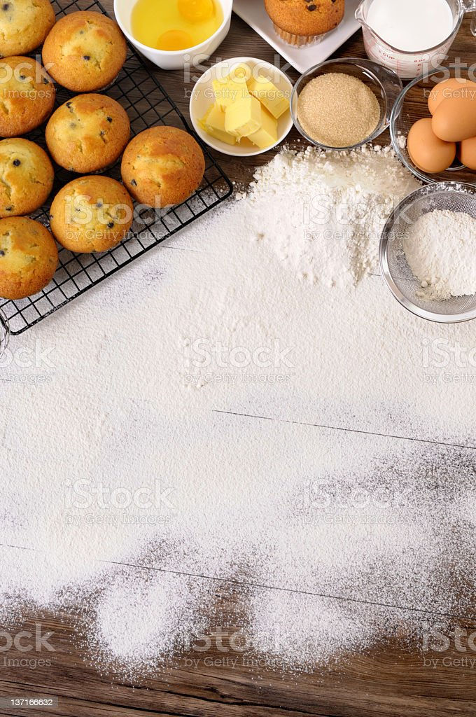 Flour on wooden table with baking ingredients on edge royalty-free stock photo