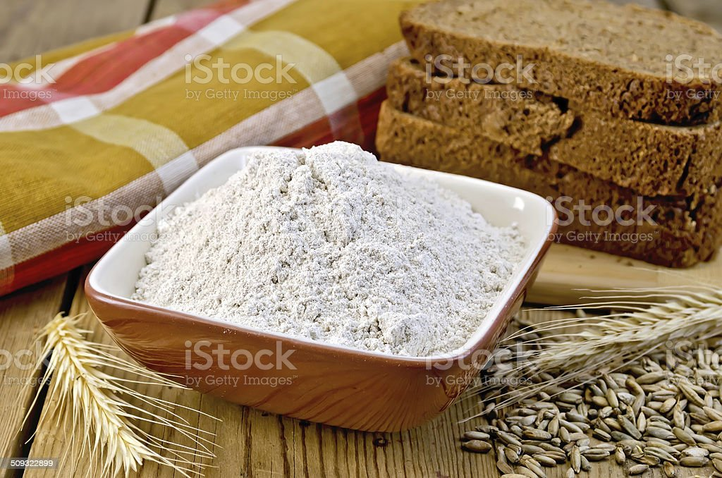 Flour rye in bowl with bread on board royalty-free stock photo