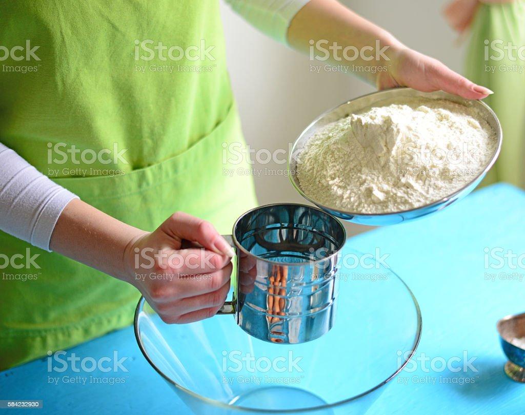 Flour sifting through a sieve for a baking stock photo