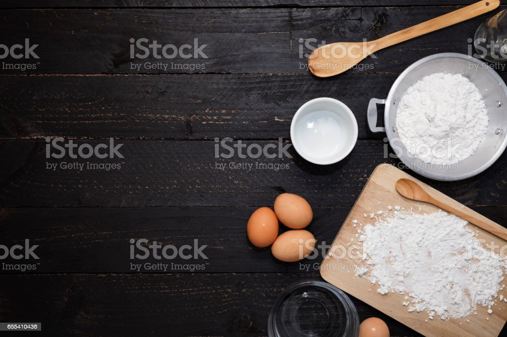 flour sprinkled with different wooden kitchen tools on black wood stock photo