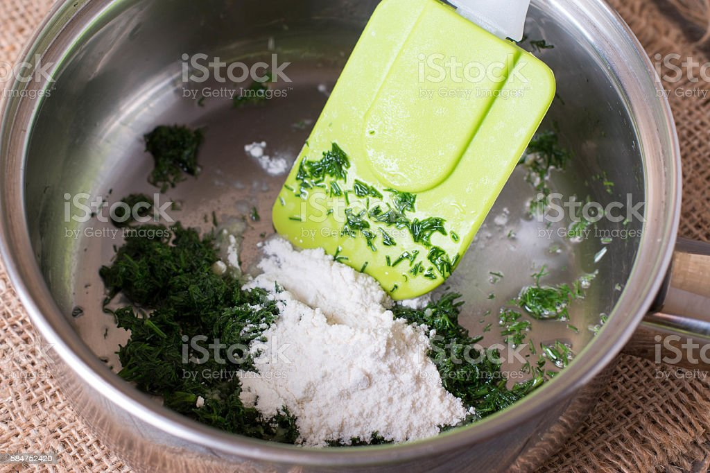 Flour with herbs in frying pan stock photo