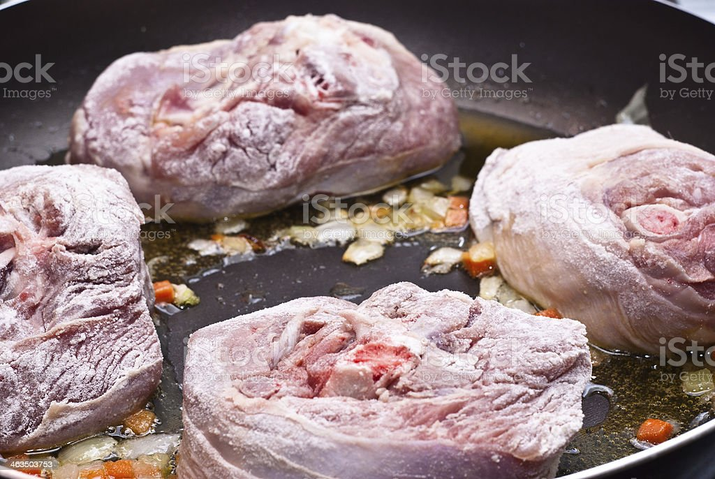 floured osso buco in pan stock photo