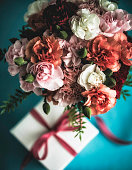 Flower arrangement with carnations, fern and gift for special occasions