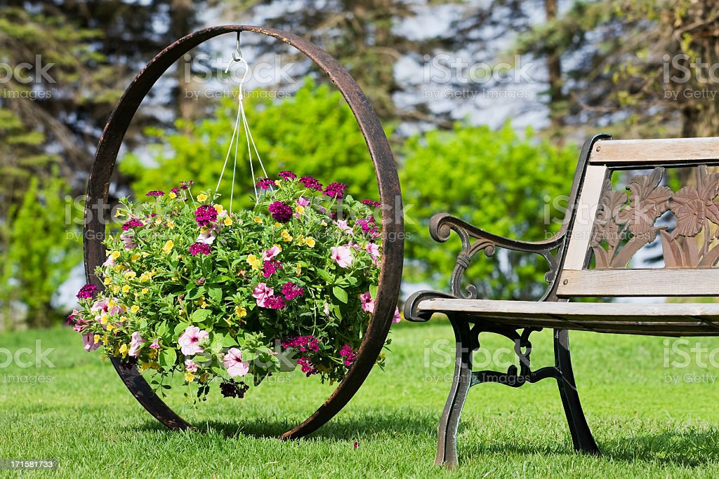 Flower Basket Hanging on Wagon Wheel by Garden Bench stock photo