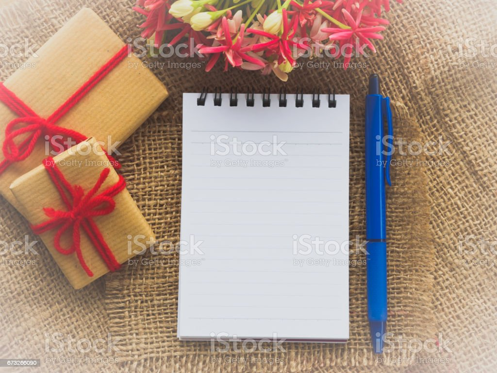 flower bouquet, gift and red flower, note book and blue pen on brown sack background stock photo