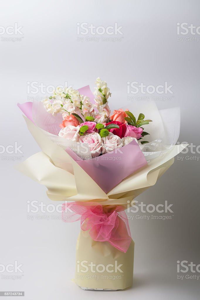 flower bouquet wrapped with paper standing on white stock photo